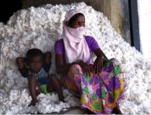 A cotton worker and her son rest in between packing cotton into a gin on the outskirts of Warangal, Telangana.