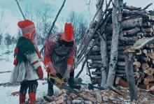 Inga Mari Hætta cutting firewood with a chain saw while her daughter Inga Ellen Kristine Hætta looks on (Northern Norway in 1974). Photo: Hugh Beach.